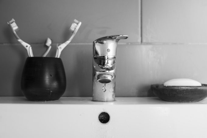 Scarce water/Black and white image of a bathroom sink with the tap dripping a drop of water, two normal toothbrushes plus a small one and a piece of soap in a soap dish.