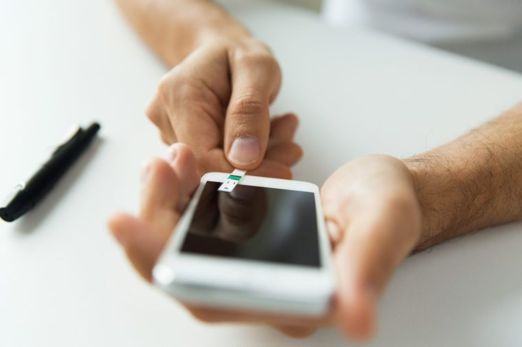 close up of man with smartphone making blood test