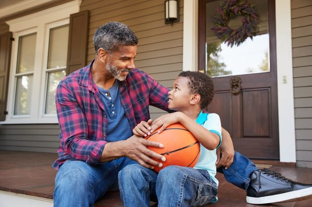 Father And Son Discussing Basketball On Porch Of Home
