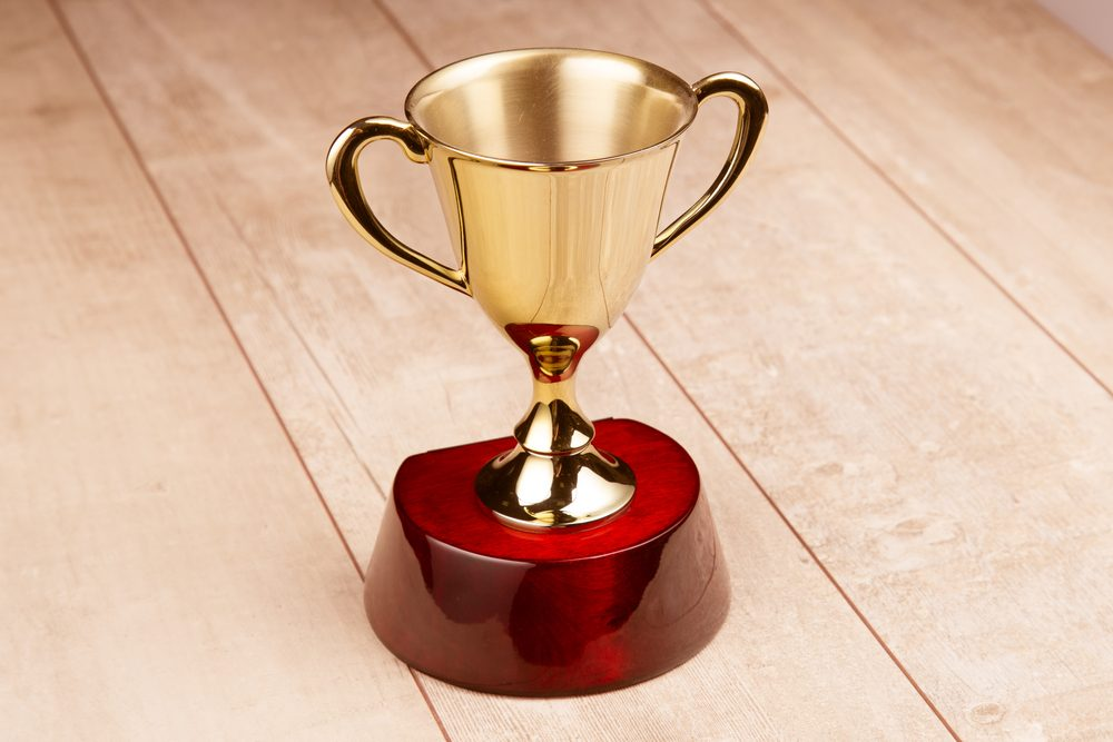 Golden trophy on wood background.