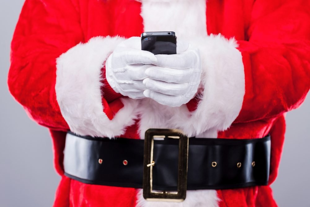 Santa Claus texting. Close-up of Traditional Santa Claus holding mobile phone while standing against grey background