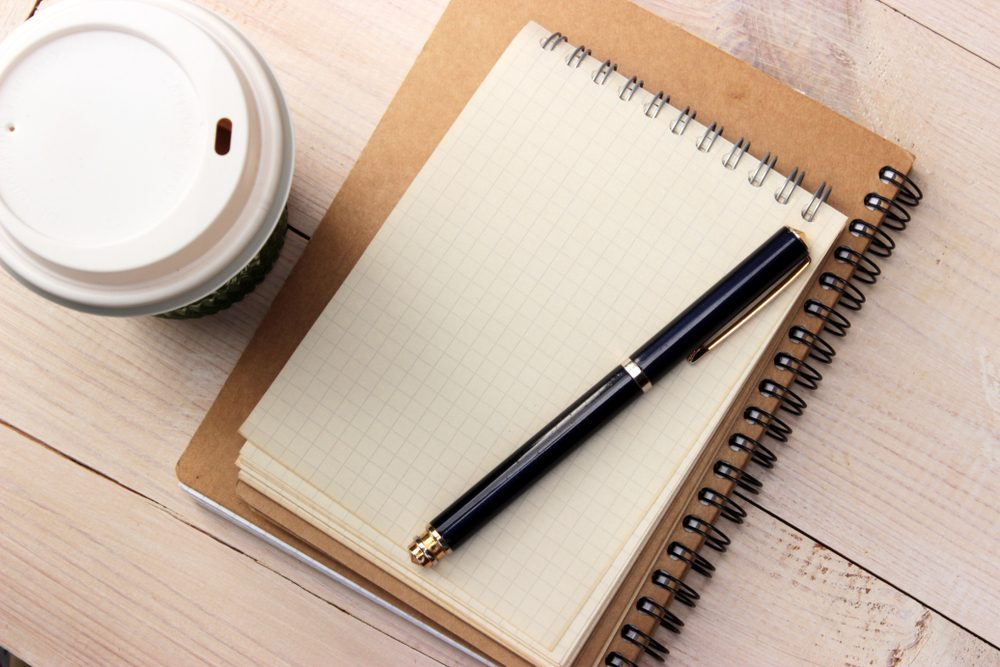 Office workplace eco style. Paper notebook, ball pen and paper cup with coffee on white wooden desk. Overhead view. Pure bright light