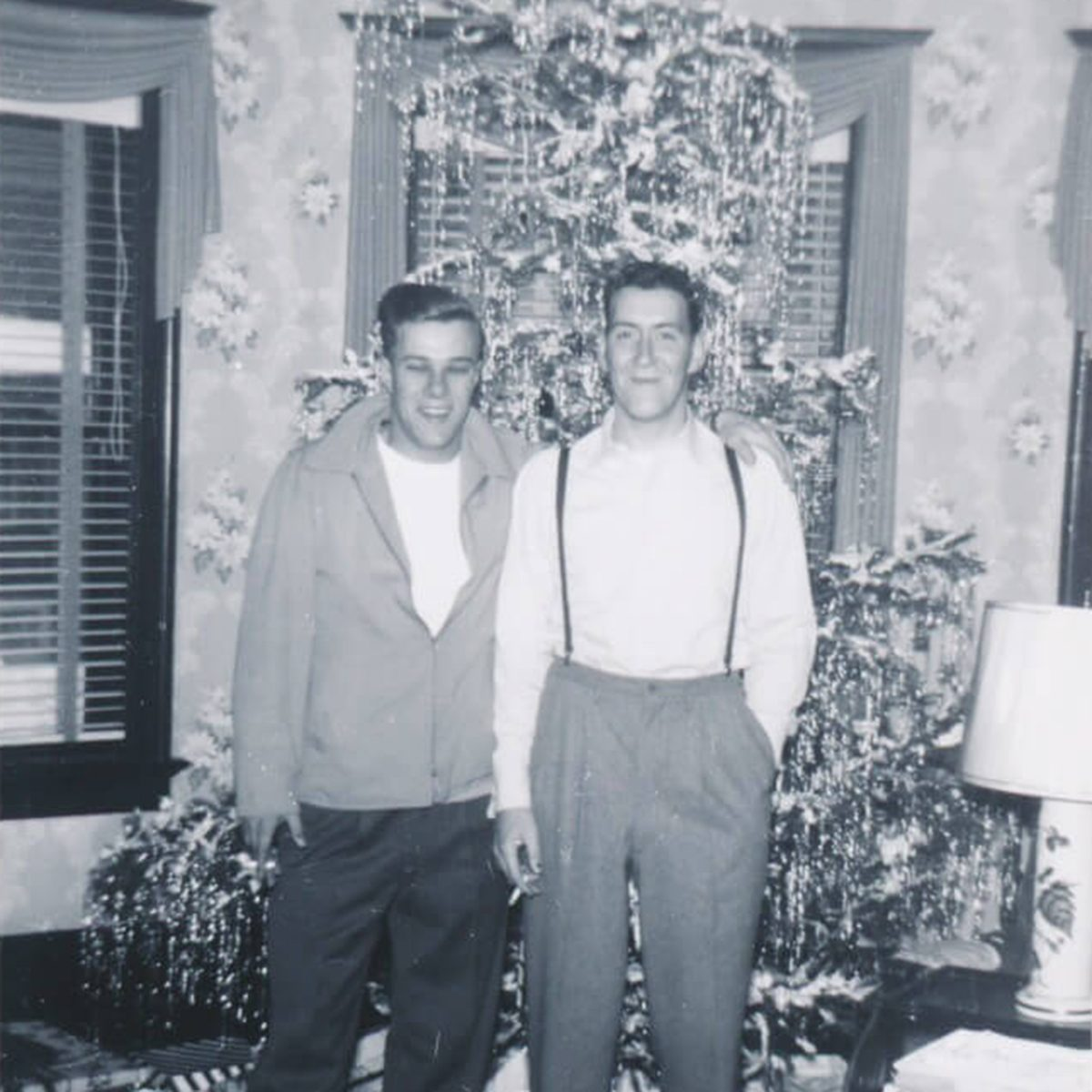 Black and white photo of two men standing in front of a christmas tree