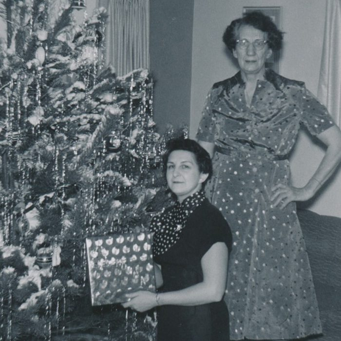 Black and white photo of two women in front of a Christmas tree