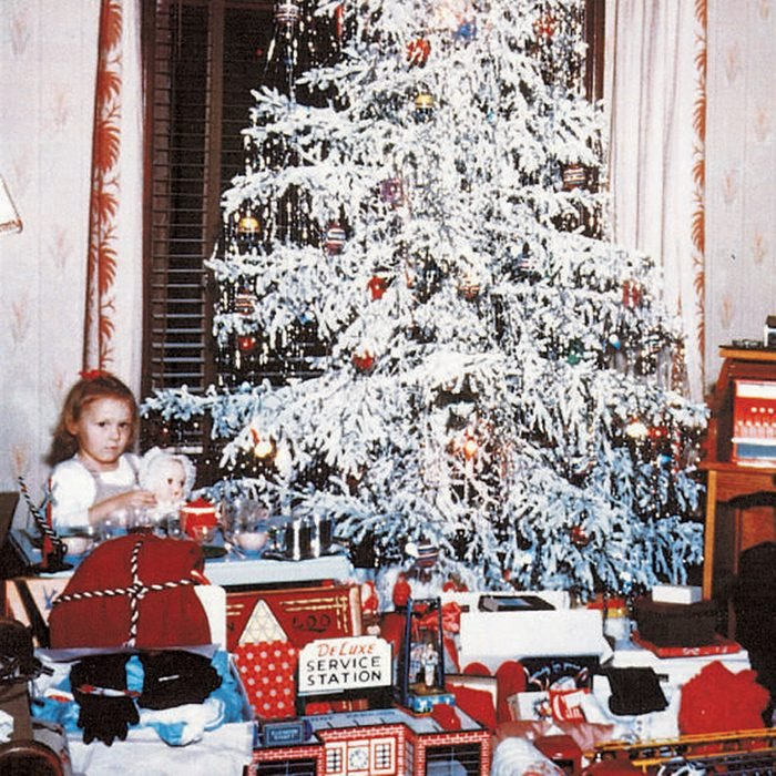 Girl and a boy sitting among opened presents under a Christmas tree
