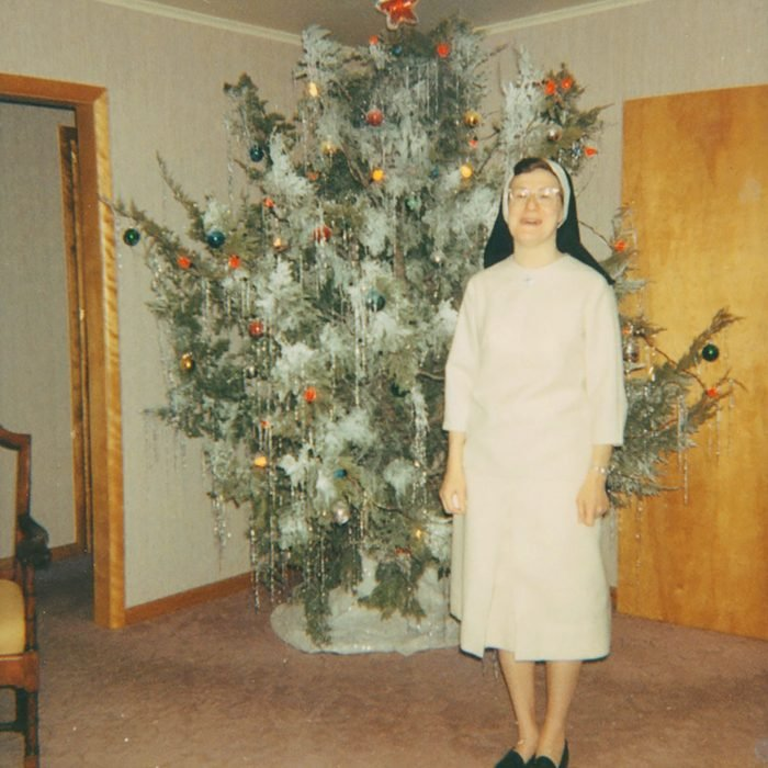 Woman standing in front of a decked out, live Christmas tree