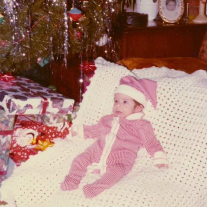 Baby laid out in front of the Christmas tree