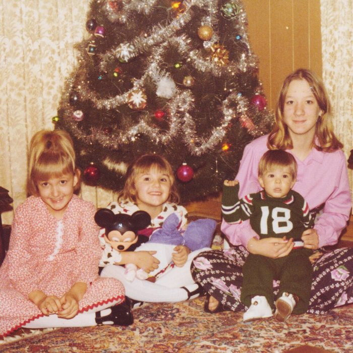 Mother and three small children in front of the Christmas tree