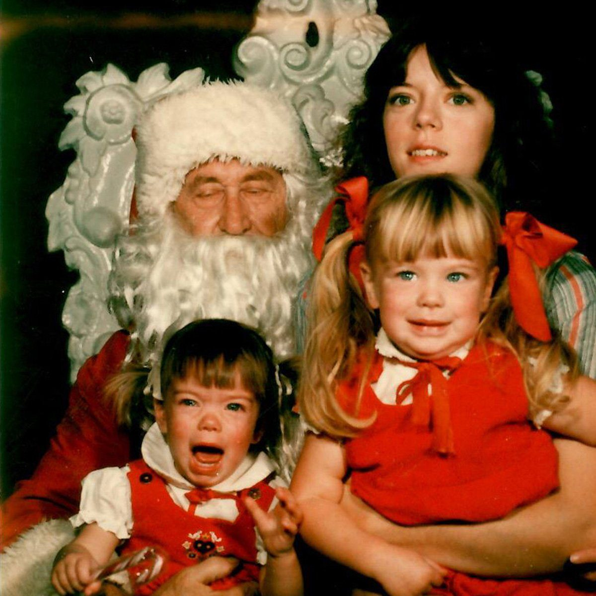 Mother and her two kids posing next to Santa