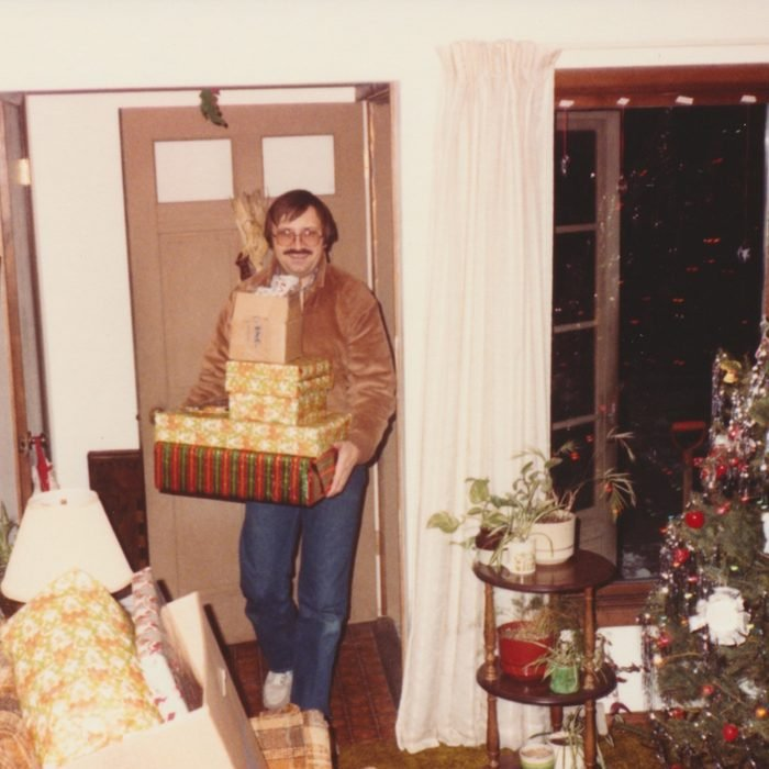 Man coming in through the front door with a present in hand