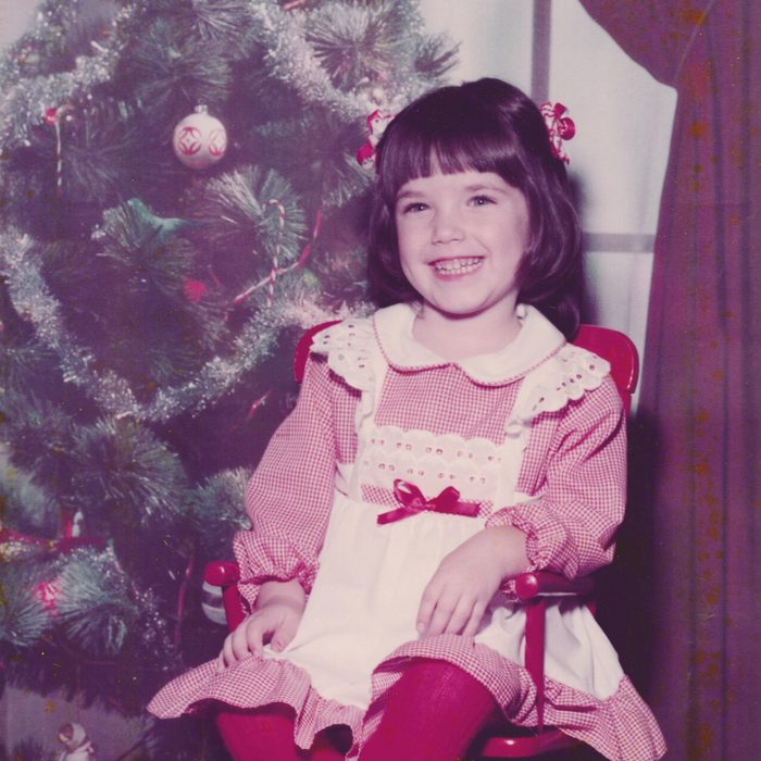 Girl posing for a picture in a red Christmas dress