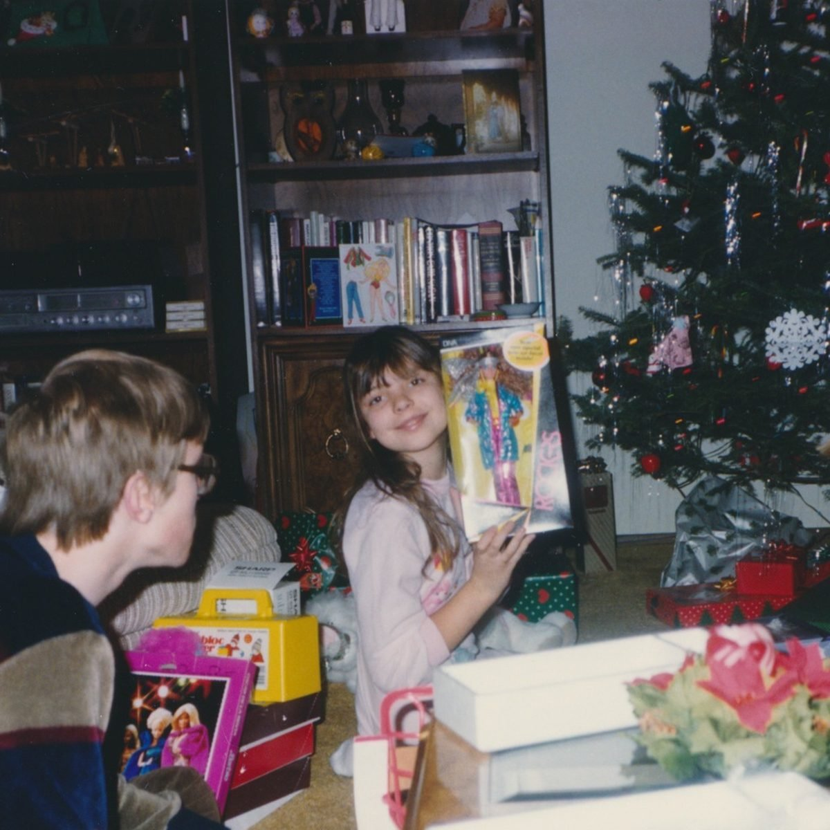 Young girl excitedly holds up Barbie she got for Christmas