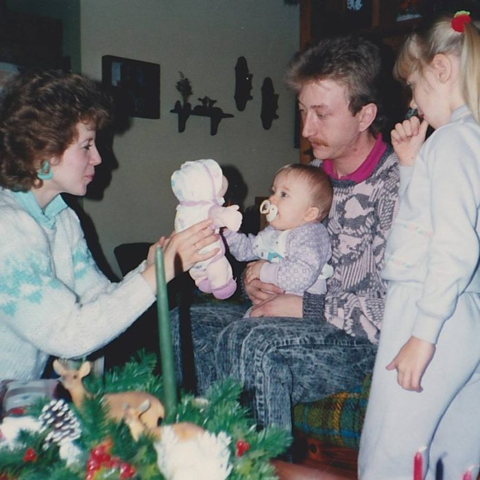 Mother, father and older sister presenting the family baby with a toy baby