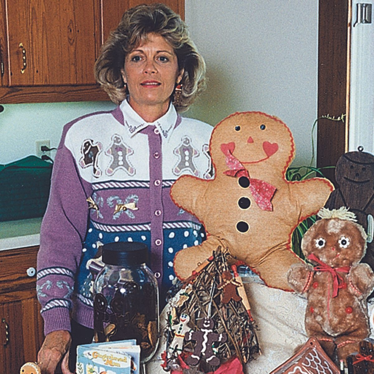Woman standing proud next to her huge gingerbread creation
