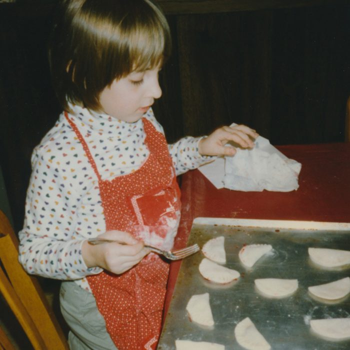 Girl diligently pinching together the ends of jam-filled cookies for Santa