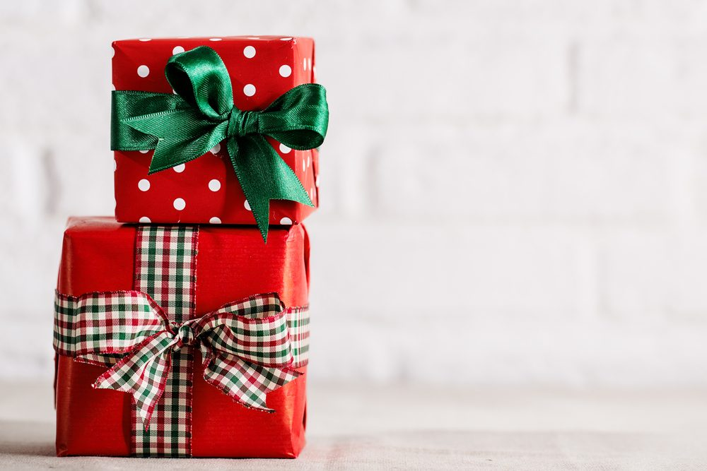 Two Christmas giftboxes in red paper wrapped with colorful ribbons composed on white background.