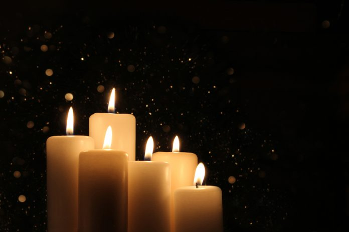 Candles Burning at Night. White Candles Burning in the Dark with lights glow. Focus on six candles in foreground.