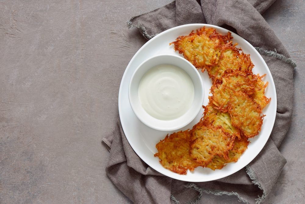 Latkes and sour cream in white plate, traditional Hanukkah dish, view from above, space for a text