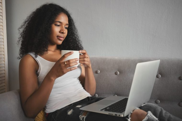 Sideways shot of fashionable attractive young dark skinned female in ripped jeans relaxing on couch with portable computer on her lap, drinking coffee and watching favorite tv series online