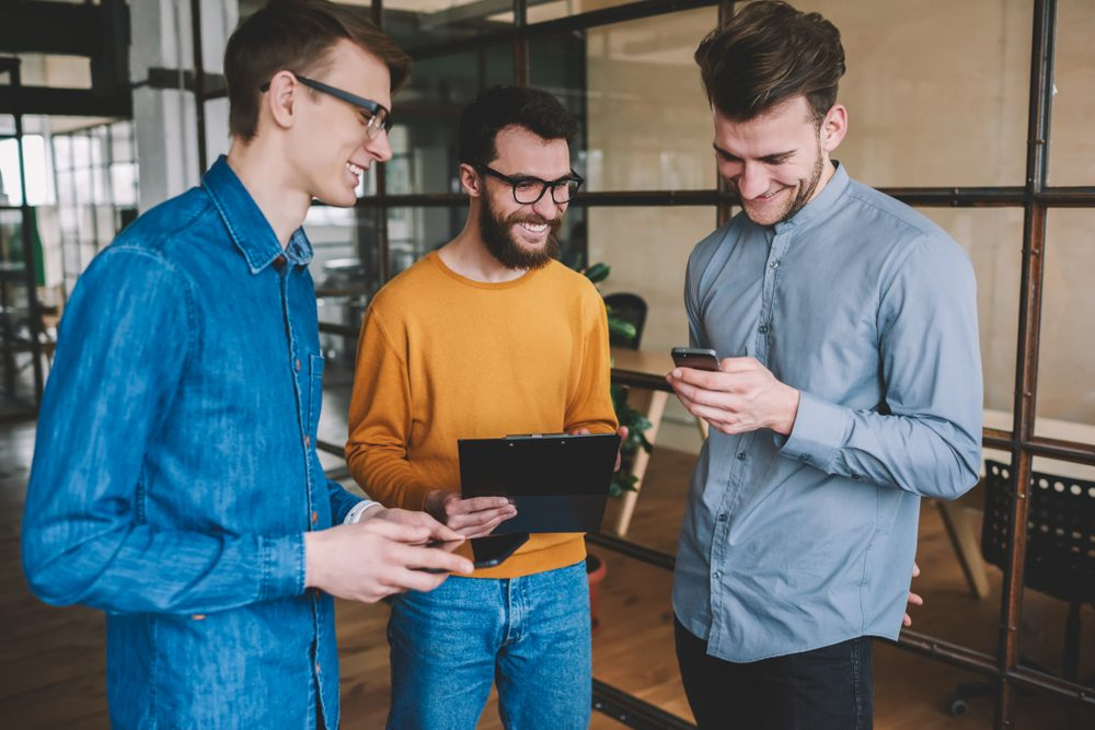 Successful male partners enjoying break of work and laughing from funny joke reading in social network via smartphone device, young positive men communicated and using technology in modern office