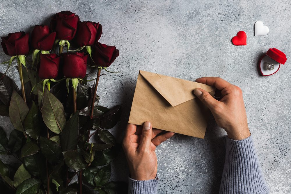 Valentines Day Man Hand Holding Envelope Love Letter With Greeting Card Mothers Red Rose Gift