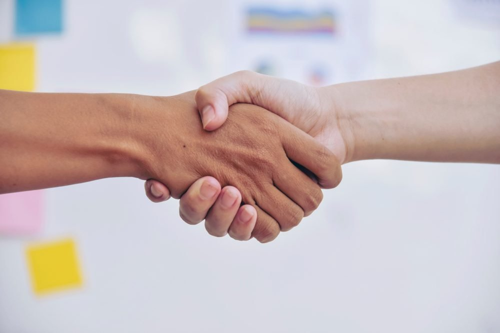Business partnership meeting concept. Image businessman handshake. Successful businessmen handshaking after good deal. Horizontal, blurred background.Split tone instagram like process.