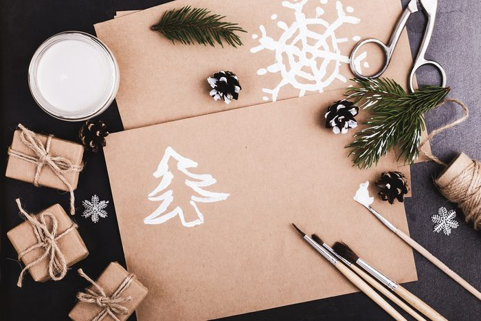 Blank of craft paper, paints and brushes on blue table with copy space for greeting text viewed from above, Christmas holiday theme