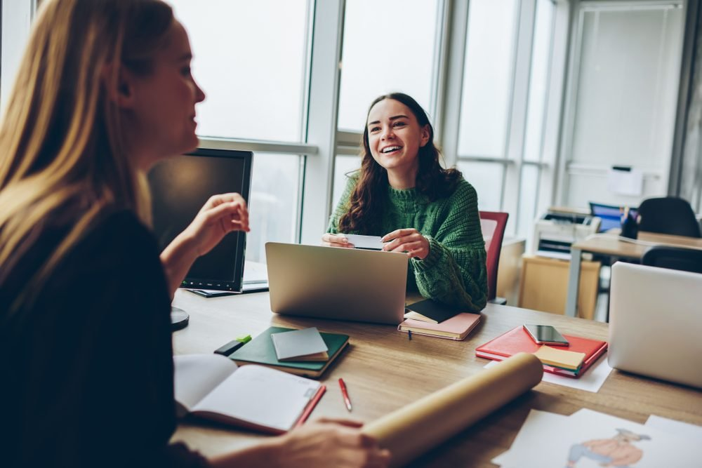 Smiling young women having fun during cooperation at desktop in office , happy female colleagues laughing at joke during working process using modern technology for collaborating on common project