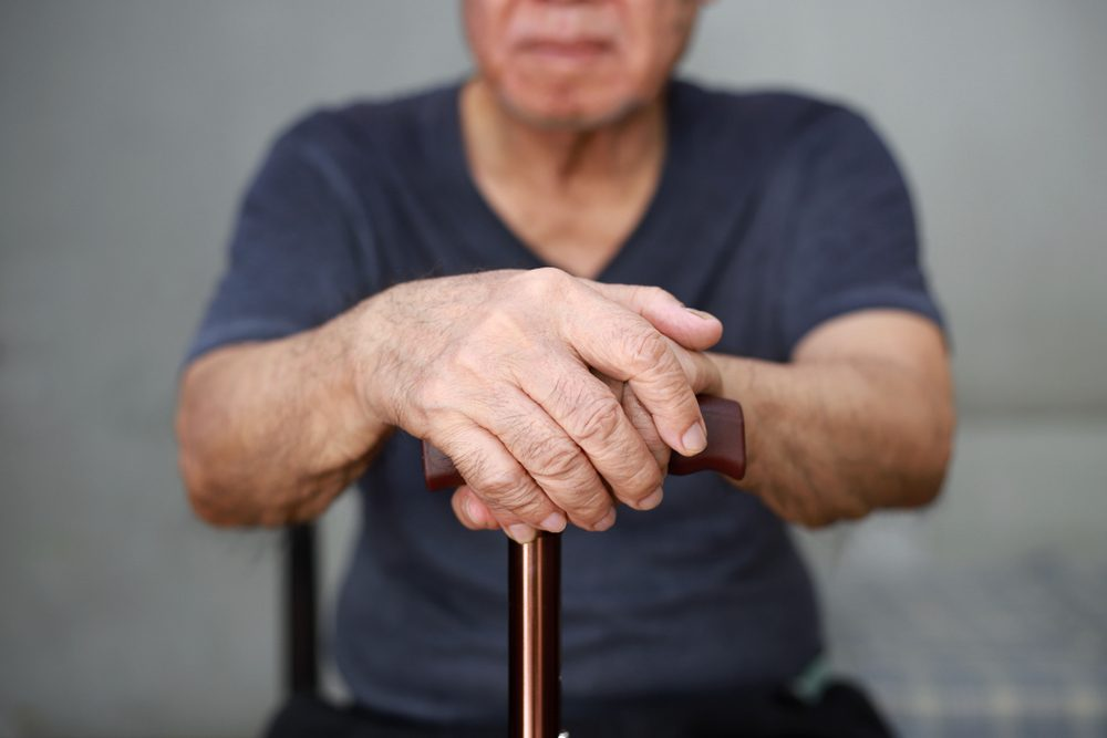 Close up of old man hand with walking stick.