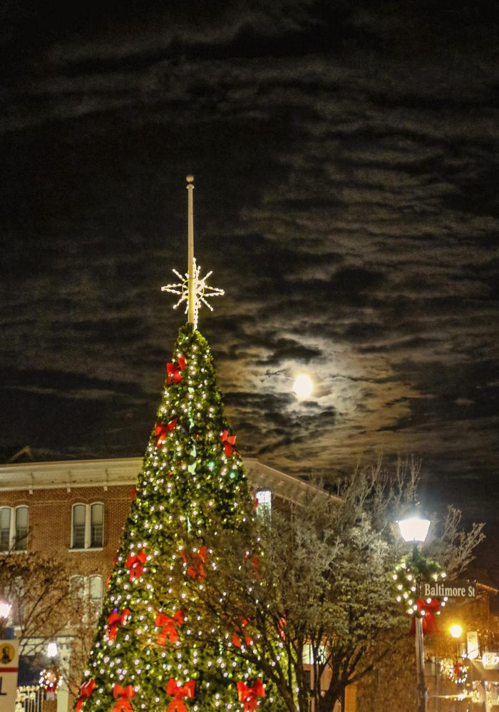 "I stopped one evening on my way home from work to get picures of the ""square"" in Gettysburg; Pennsylvania - it is always decorated so nicely at Christmastime. After about a half an hour or so - and some cold hands - I decided it was time to head home. I turned around to take one last picture and noticed that the full moon that had been hidden behind clouds until that point had decided to peek out. I was able to get this picture of the moon shining brightly in the background behind the Christmas tree."
