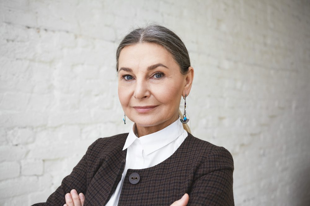 Close up shot of successful beautiful confident senior businesswoman in her fifties with gray hair and blue wise eyes posing indoors, keeping arms folded, looking at camera with charming smile