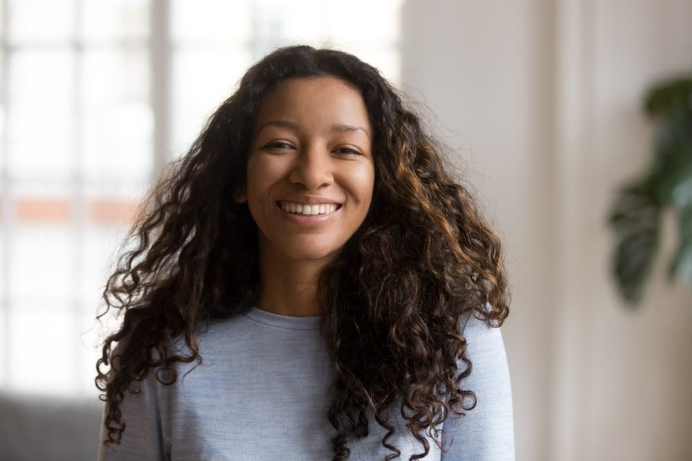 Head shot portrait attractive African American smiling woman, happy pretty female with fluffy curly hair, successful millennial person, standing, posing in living room, looking at camera
