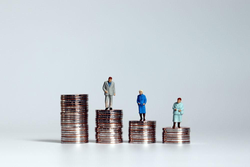 Concepts on aging society and increasing costs. The pile of coins and miniature people.