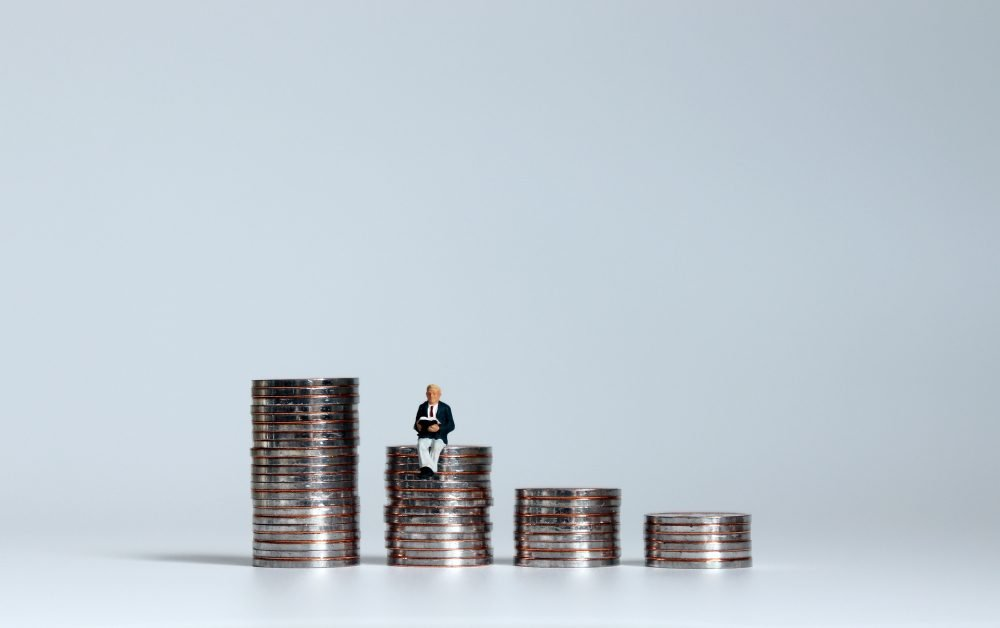 The concept of a retirement fund plan. The pile of coins and miniature people.