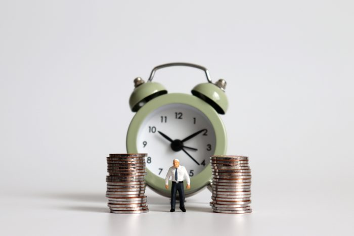 Miniature old man standing with a pile of coins in front of the alarm clock.