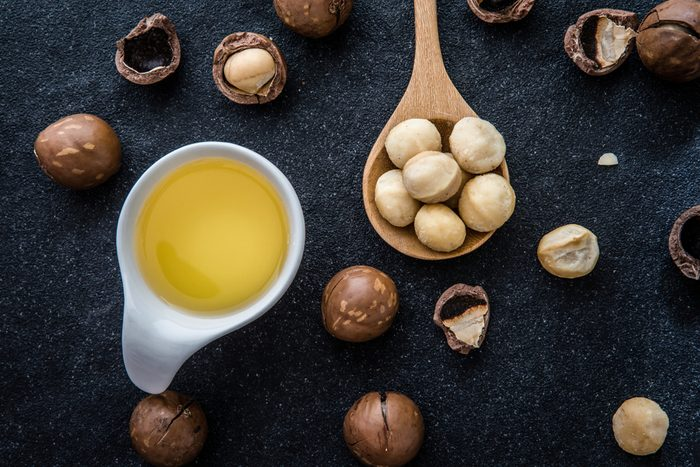 Macadamia Nut Oil and peeled macadamia nut on black stone , use for Healthy Skin and Hair and Natural Healing Oil Treatment , overhead and top view