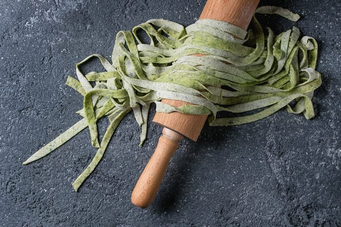 Fresh raw uncooked homemade green spinach pasta tagliatelle on wooden rolling pin over dark texture concrete background. Top view with space.