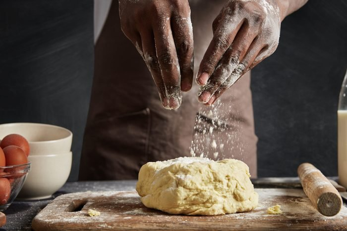Indoor shot of African male wears apron, makes dough for baking bread, uses flour, eggs and other ingridients, works on kitchen table with rolling pin. professional cook shows his culinary talents