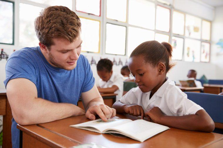 Volunteer teacher helping schoolgirl at her desk, close up
