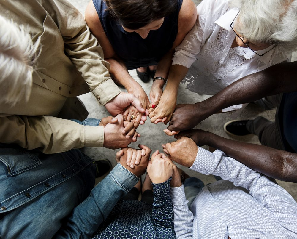 Group of diverse hands holding each other support together teamwork aerial view
