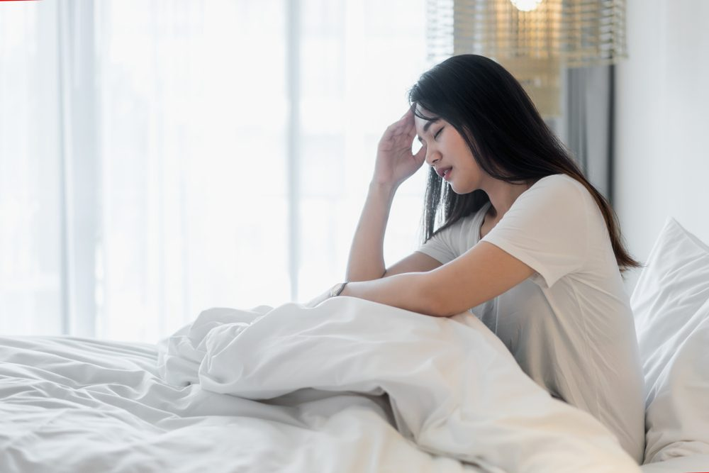 Attractive young Asian woman wake up on her bed looking unhappy and feeling sick.