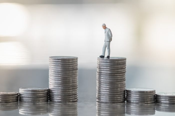 Money and Business Concept. Businessman miniature figure standing, looking and thinking from the top of stack of coins