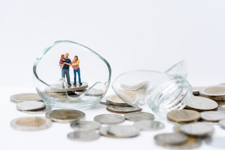 Miniature people, family standing on broken glass of jar filled with coins, financial, money saving, bankrupt, investment concept.