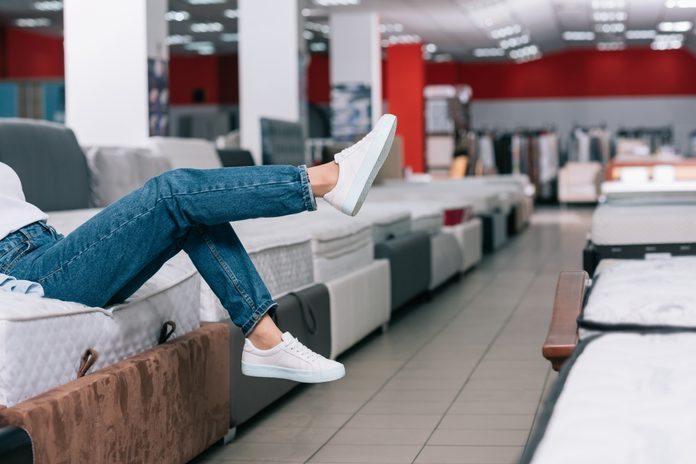 partial view of woman sitting on mattress in furniture shop