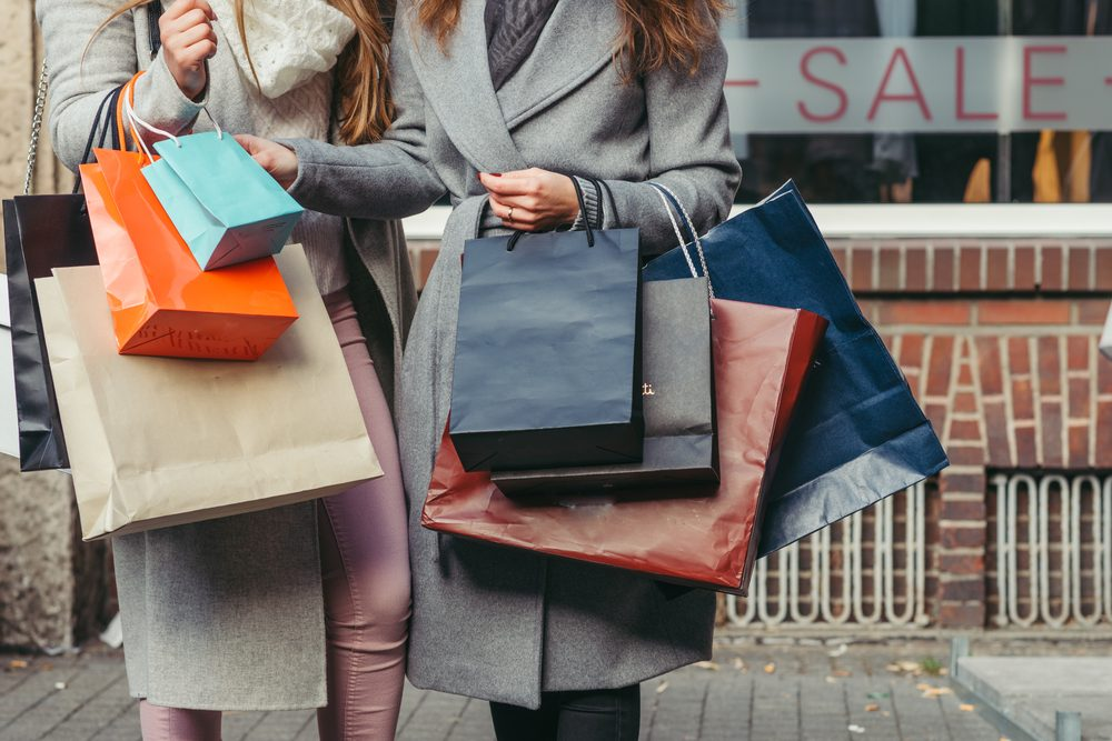 two girls with shopping bags in front of show-window with sale written on it, close up
