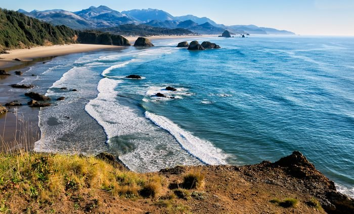 Sweeping view of the Oregon coast, miles of white sandy beaches, sea stacks and ocean waves. Location: Cliff's edge at Ecola Park overlook in the Pacific Northwest, USA