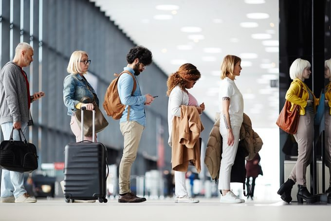 Side view of multiracial people standing in queue to check in in airport hall