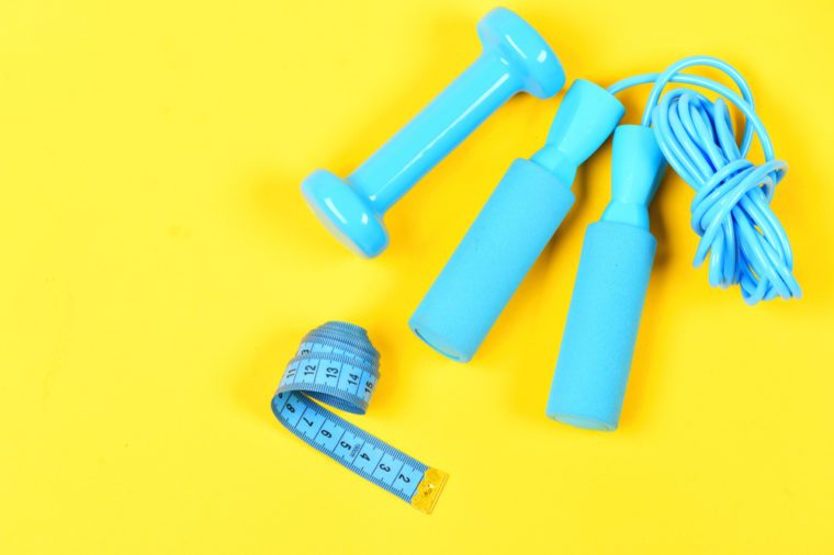 Gym and healthy lifestyle tools. Weight loss and sports concept. Dumbbell, twisted measuting tape and jumping rope lay top on yellow background. Centimeter in blue color near colorful sport equipment.