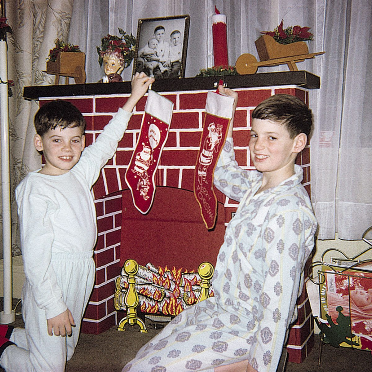 Boys holding stockings over fireplace