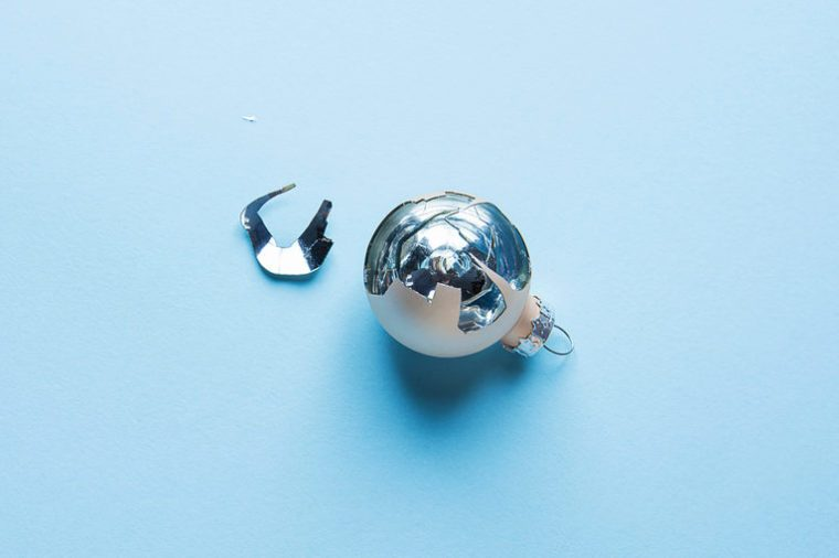 Broken Christmas Tree Ornament Ball on Blue Background. Splinters Glittering. Luck Hope Concept. Superstition.